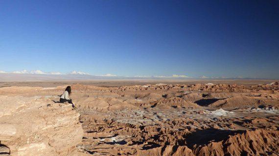 Mulher sentada observando o Valle de la Luna