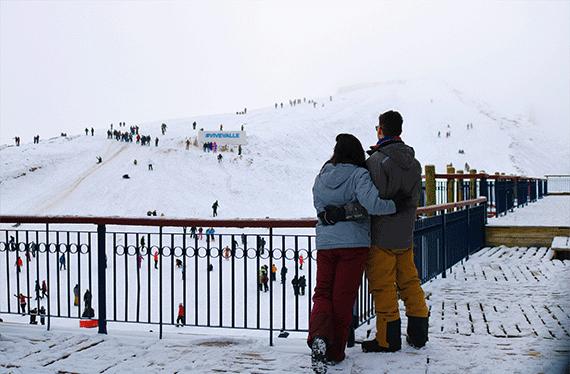 casal em valle nevado no chile vendo viajantes esquiar